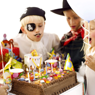 Children (6-10) Wearing Costumes and Blowing Out Candles on Birthday Cake --- Image by © Royalty-Free/Corbis